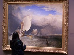 Honors student looks at a painting by J.M.W.
