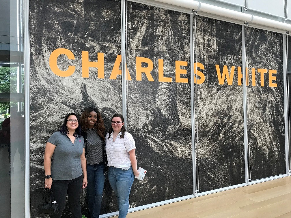 Three students standing in front of an exhibit for Charles White,an American artist known for his chronicling of African American related subjects in paintings, drawings, lithographs, and murals.
